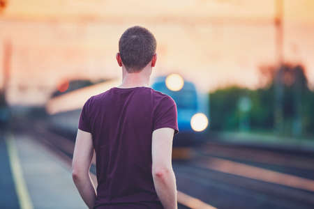 Traveling by train. Young man waiting on the platform oft railway station.