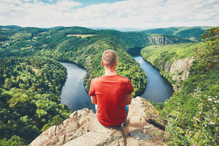 Man on the top of the hill. Young tourist enjoying view on the river. Vltava river, Czech Republic