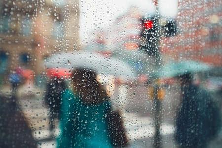 Düsterer Tag in der Stadt. Menschen bei starkem Regen. Selektiver Fokus auf die Regentropfen. Prag, Tschechische Republik.