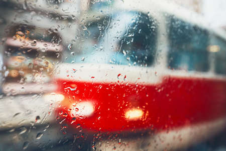 Gloomy day in the city. Tram on the street in rain. Selective focus on the raindrops on the window. Prague, Czech Republic. Banco de Imagens
