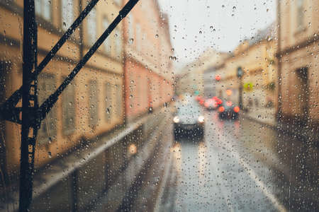 Gloomy day in the city. Street in rain. Selective focus on the raindrops on the window. Prague, Czech Republic.
