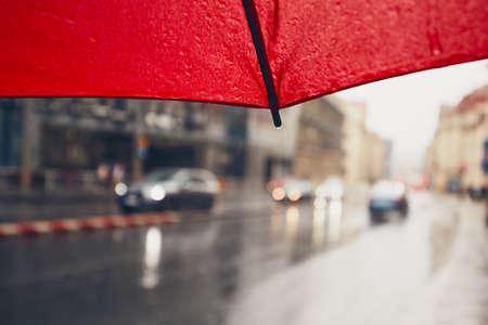 gloom: Gloomy day in the city. Traffic in heavy rain. Selective focus on the umbrella. Prague, Czech Republic.