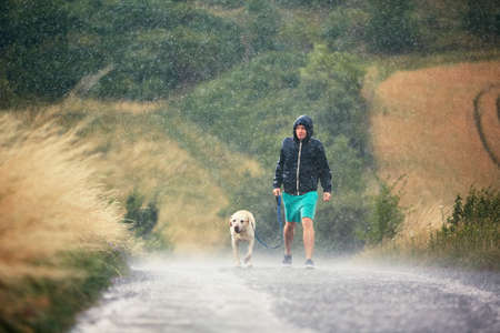 Young man walking with his dog (labrador retriever) in heavy rain on the rural road.