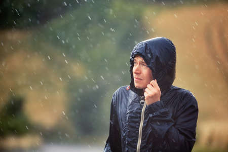 Young man walking in nature during heavy rain. Stock Photo