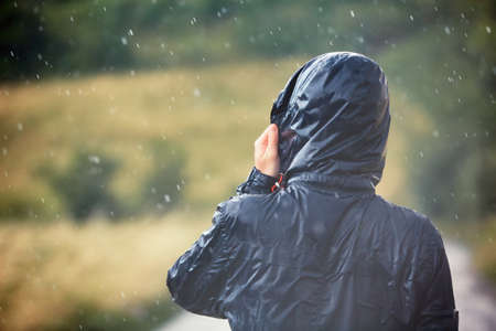 Young man walking in nature during heavy rain. Banque d'images