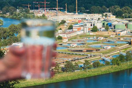 Glass of drinking water and sewage treatment plant - selective focus