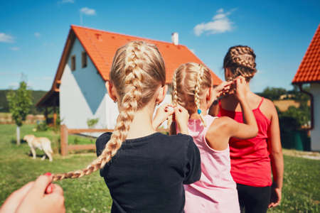 Girls each to other making hair braids of the little girl on the garden in the countryside.