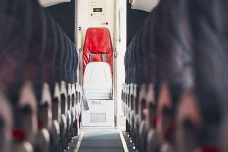 エコノミー クラスおよび商業飛行機の客室乗務員用のジャンプ シートで通路。 写真素材
