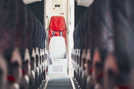 Aisle in economy class and jump seat for cabin crew in the commercial airplane. 版權商用圖片