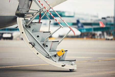 開いたドアが付いている飛行機は忙しい空港で搭乗の乗客の準備ができて。