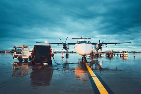 비가 내리는 바쁜 공항. 비행 전에 프로 펠 러 비행기의 준비.