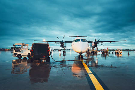 A busy airport in the rain. Preparation of the propeller airplane before flight.