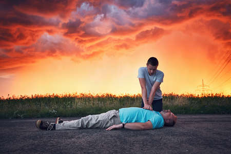 Dramatic resuscitation on the road during storm at the spectacular colorful sunset. Themes rescue, help and hope.