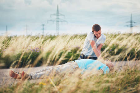 Young man calling for Emergency medical service. Dramatic resuscitation on the rural road. Themes rescue, help and hope. Stock Photo