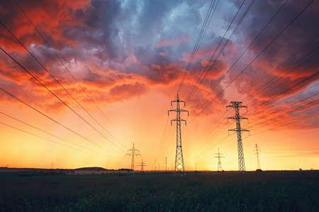 Gevaarlijk weer. Elektriciteitsmasten met machtslijnen in overweldigende storm tijdens kleurrijke zonsondergang.