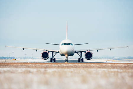 Airport in winter. Airplane taxiing to the runway for take off. Imagens