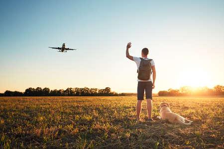 Zeg hallo tegen de zonsondergang. Jonge man met zijn hond op de avondwandeling langs de luchthaven.