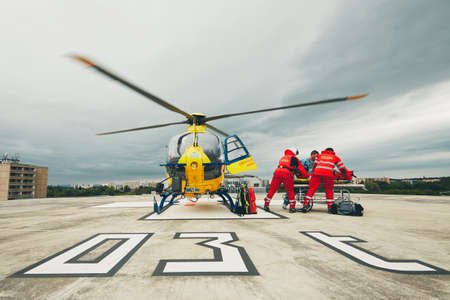 HRADEC KRALOVE, CZECH REPUBLIC - JUNE 17, 2017: Team of the Helicopter Emergency Medical Service passes the patient to the Emergency on the roof University Hospital in Hradec Kralove on June 17, 2017. 報道画像