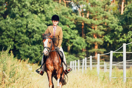 Teenage girl in formal wear riding a horse in nature. Reklamní fotografie