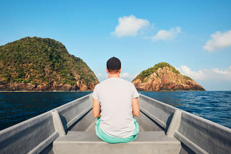 Rear view of young man while traveling in boat on sea against tropical islands and blue sky.