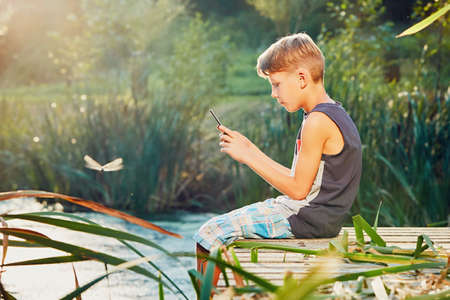 Summertime in the countryside. Boy sitting on the pier of the lake. Little photographer taking photo of the dragonfly by smart phone camera.