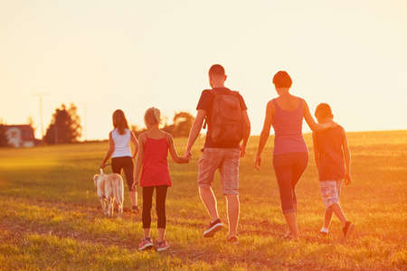 Summertime in the countryside. Silhouettes of the family with dog on the trip at the sunset. Stockfoto