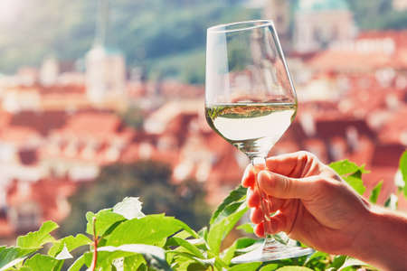Hand of the man holding glass of white wine. Relaxation in Prague, Czech Republic.