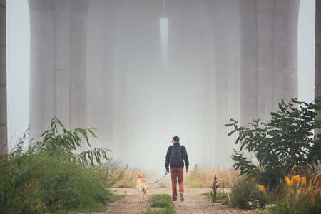 Man with dog under highway bridge in mysterious morning fog. Prague, Czech Republic 版權商用圖片