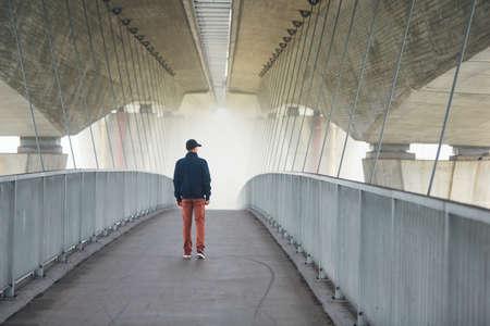 Man on the footbridge under highway bridge in mysterious morning fog. Prague, Czech Republic Stock Photo