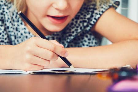 초등학교에 대 한 그의 숙제를 작성하는 어린 소녀.