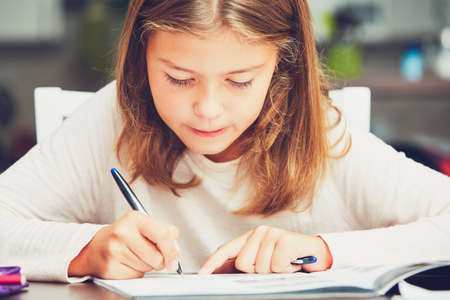 Little girl writing his homework for elementary school. Stock Photo