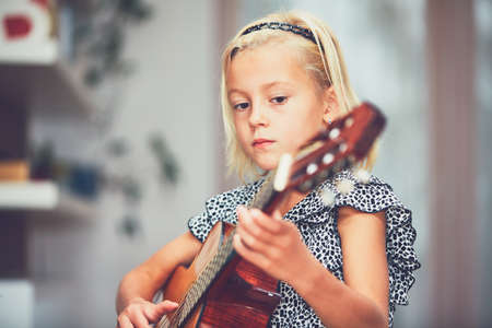Little girl learning to play to the guitar at the home.