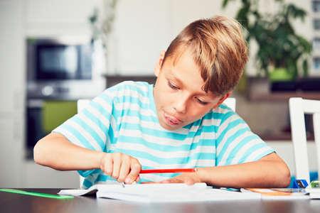 초등학교에 자신의 숙제를 작성하는 어린 소년.