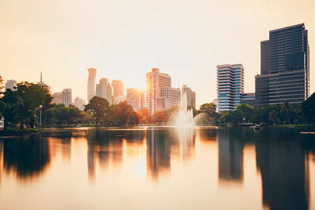 Urban skyline of Bangkok with reflection in the lake waters at the sunset. Banco de Imagens