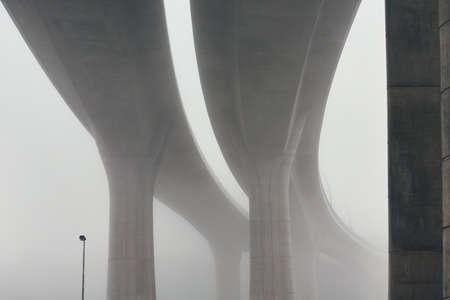 Pillars of the highway bridge in mysterious morning fog. Prague, Czech Republic