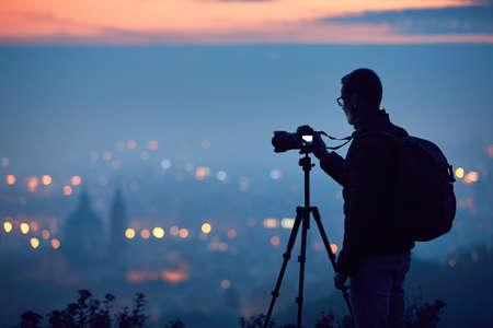 Sylwetka fotografa ze statywem. Młody człowiek bierze fotografię z jego kamerą w nocy mieście. Praga, Republika Czeska. Zdjęcie Seryjne