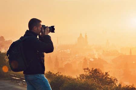 日の出の写真。若い男は街のスカイラインの写真を撮影。プラハ、チェコ共和国。