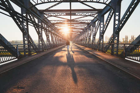 Morning walk across the river. Silhouettes and shadows of the man with dog on the iron bridge. Stock Photo