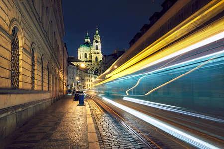 Night traffic on the ancient street near The Church of Saint Nicholas in Prague, Czech Republic.