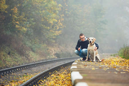 Old railway station in fog. Autumn mood on the trip. Young man traveling with his dog by train.