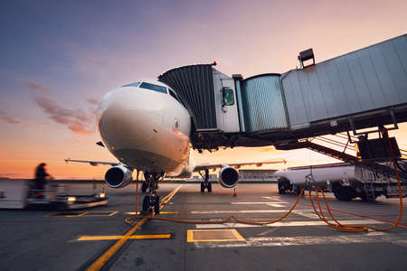 Busy airport at the colorful sunset. Preparation of the airplane before flight.