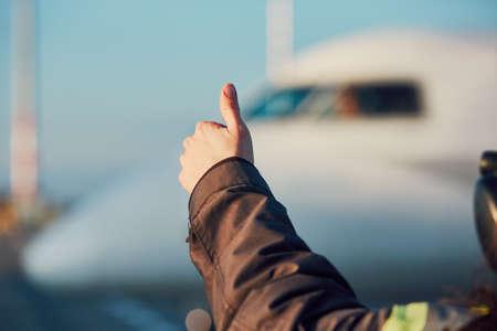 공항에서 화창한 날. 지상 승무원의 구성원 이륙하기 전에 조종사에 확인 표시를 보이고있다.