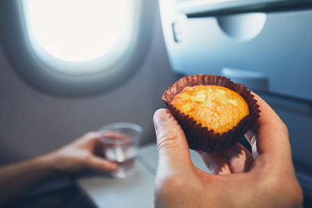 Comfortable traveling by airplane. Passenger is holding muffin and drinking glass with water during the flight. Imagens
