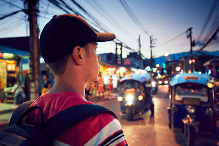 Young man walking on the busy street full of shops - Chiang Mai, Thailand Foto de archivo