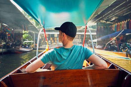 Young man (traveler) on the boat. Traditional floating market Damnoen Saduak in Ratchaburi near Bangkok, Thailand.
