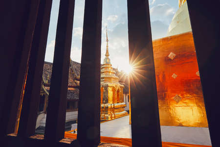 View from the window of the buddhist Phra Singh Temple at the sunset. Tourists favorite landmark in downtown Chiang Mai in Thailand.