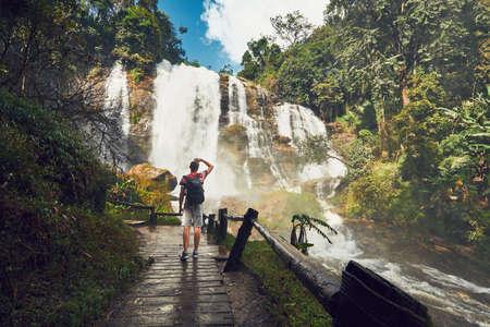 Young man (traveler) standing near Wachirathan waterfall in tropical rainforest. Chiang Mai Province, Thailand