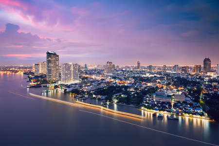 Bangkok during dusk. City skyline with traffic (boats in blurred motion) on the Chao Phraya River.  Stock Photo
