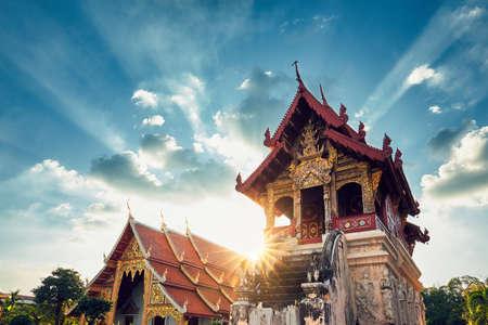Buddhist Phra Singh Temple at amazing sunset. Tourists favorite landmark in Chiang Mai city centre, Thailand. Standard-Bild