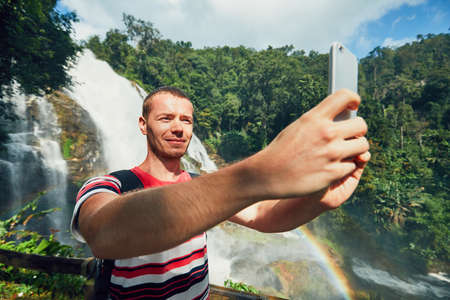 Young tourist taking a selfie against Wachirathan waterfall. Chiang Mai Province, Thailand.